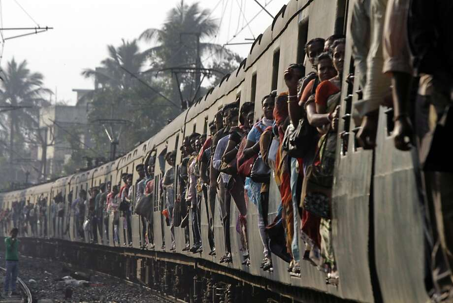 Indian commuters travel in a local train in Kolkata, India, Tuesday, Feb. 26, 2013. Indian Railway Minister Pawan Kumar Bansal is presenting the country's rail budget for next fiscal year in the parliament Tuesday, Feb. 26, 2013. Indian railway network is one of the world's largest, with some 14 million passengers daily and some 64,000 kilometers (40,000 miles) of railway track cut through some of the most densely populated cities. (AP Photo/Bikas Das) Photo: Bikas Das, Associated Press