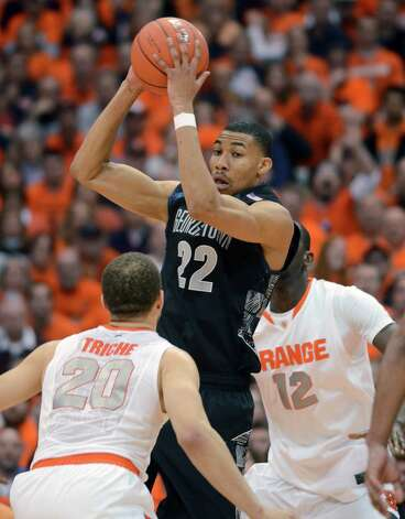 Georgetown's Otto Porter grabs a rebound in front of Syracuse's Brandon Triche during the second half in an NCAA college basketball game in Syracuse, N.Y., Saturday, Feb. 23, 2013. Georgetown won 57-46. (AP Photo/Kevin Rivoli) Photo: Kevin Rivoli, Associated Press / FR60349 AP