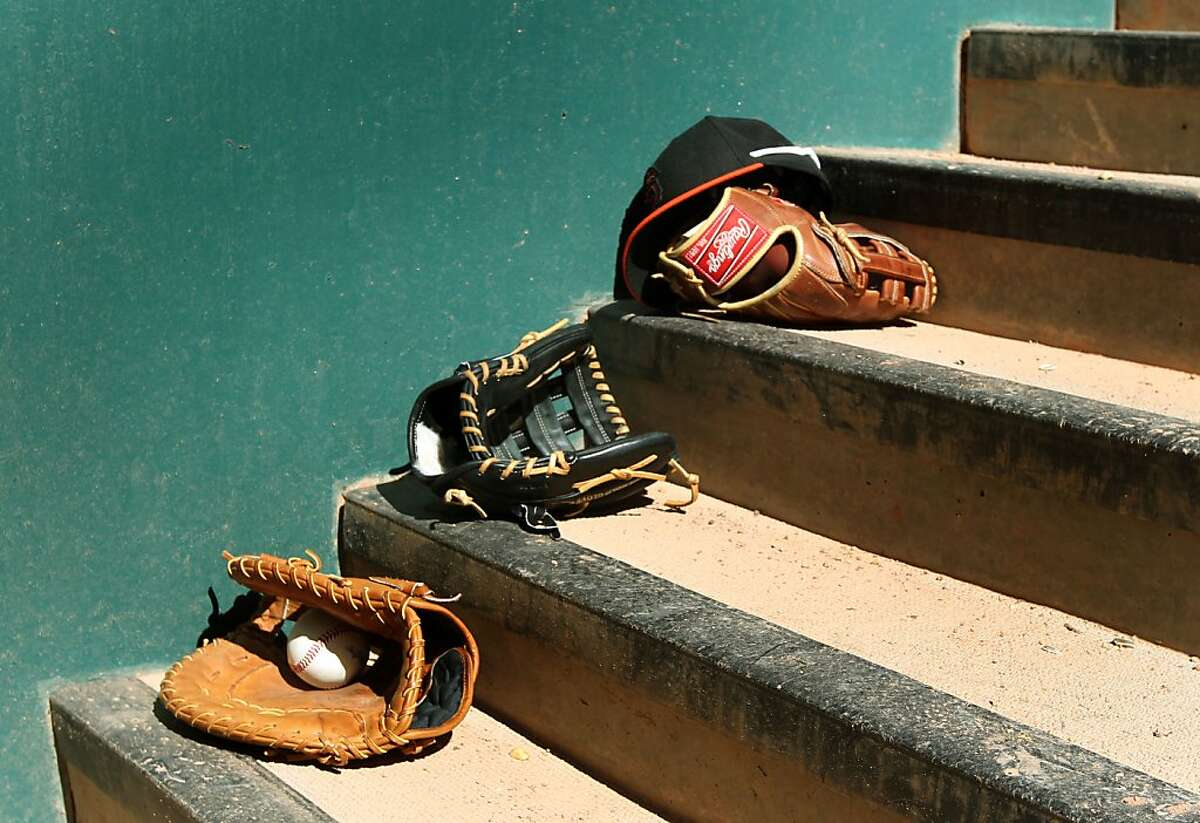 Players' gloves rest on the steps inside the Giants' dugout during a spring training game last week.