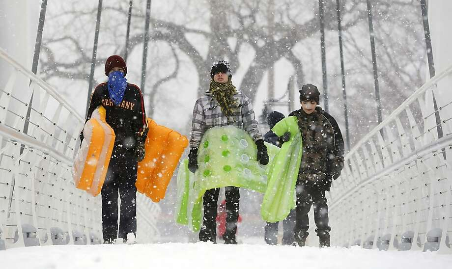 Chance Cain, from left, Simon Mourning and Nathan Talley walk towards a sledding hill near downtown Wichita, Kan. as a winter storm moves through the area on Monday, Feb. 25, 2013. (AP Photo/The Wichita Eagle, Travis Heying) LOCAL TV OUT; MAGS OUT; LOCAL RADIO OUT; LOCAL INTERNET OUT Photo: Travis Heying, Associated Press