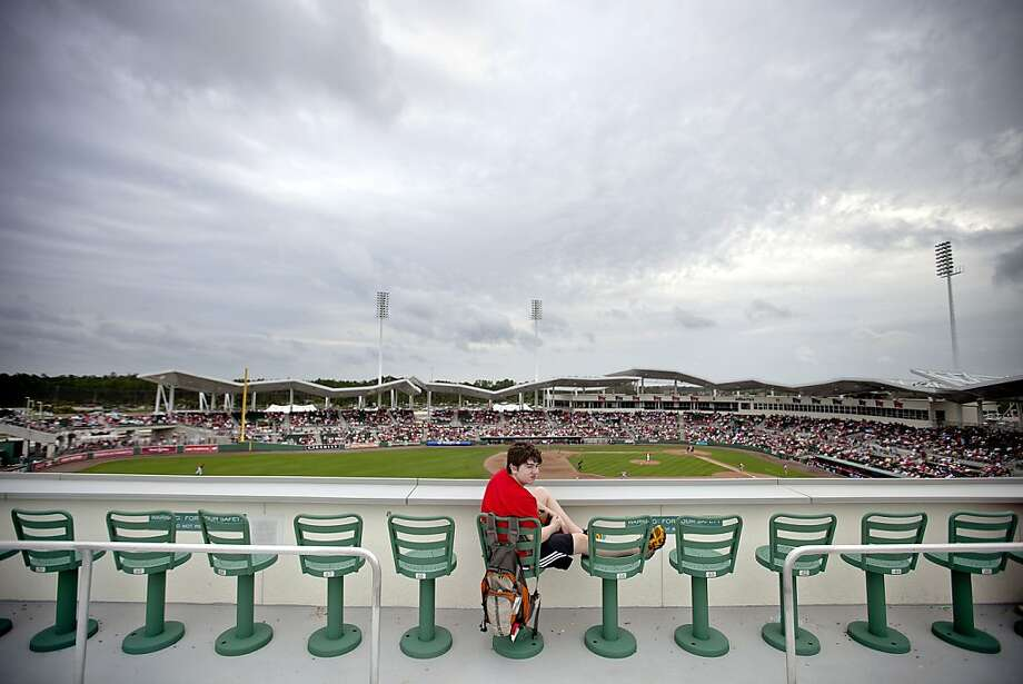 Barton Murray, 13, of Boston, sits atop the outfield wall waiting to catch a ball in the seventh inning of a spring training baseball game between the Boston Red Sox and the St. Louis Cardinals, Tuesday, Feb. 26, 2013, in Fort Myers, Fla. (AP Photo/David Goldman) Photo: David Goldman, Associated Press