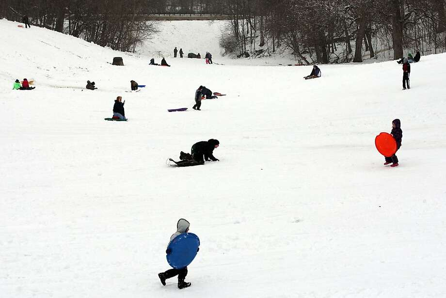 Children and parents take advantage of school cancellations by sledding Tuesday Feb. 26, 2013 at Perkins Park in Burlington, Iowa. The Burlington area saw about 4-5 inches of snow accumulation during Tuesday's storm.  (AP Photo/The Hawk Eye, Brenna Norman) Photo: Brenna Norman, Associated Press