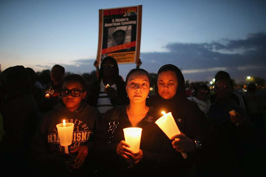 SANFORD, FL - FEBRUARY 26:  Apollonia Mitchell, Shenika Mitchell and Yolanda Pearson (L-R) gather with others for a candle light vigil at Fort Mellon Park to mark the one year anniversary of when Trayvon Martin was killed on February 26, 2013 in Sanford, Florida. Martin was shot by George Zimmerman on February 26, 2012 while Zimmerman was on neighborhood watch patrol in the gated community of The Retreat at Twin Lakes in Sanford, Florida. (Photo by Joe Raedle/Getty Images) Photo: Joe Raedle, Getty Images
