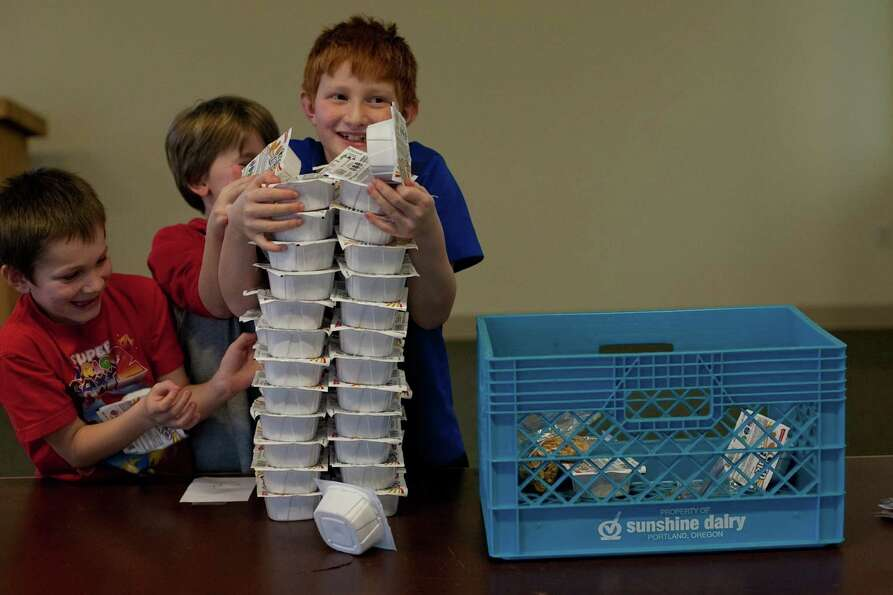 Aidan Cummings, 8, tries to keep cereal packages from toppling over during a