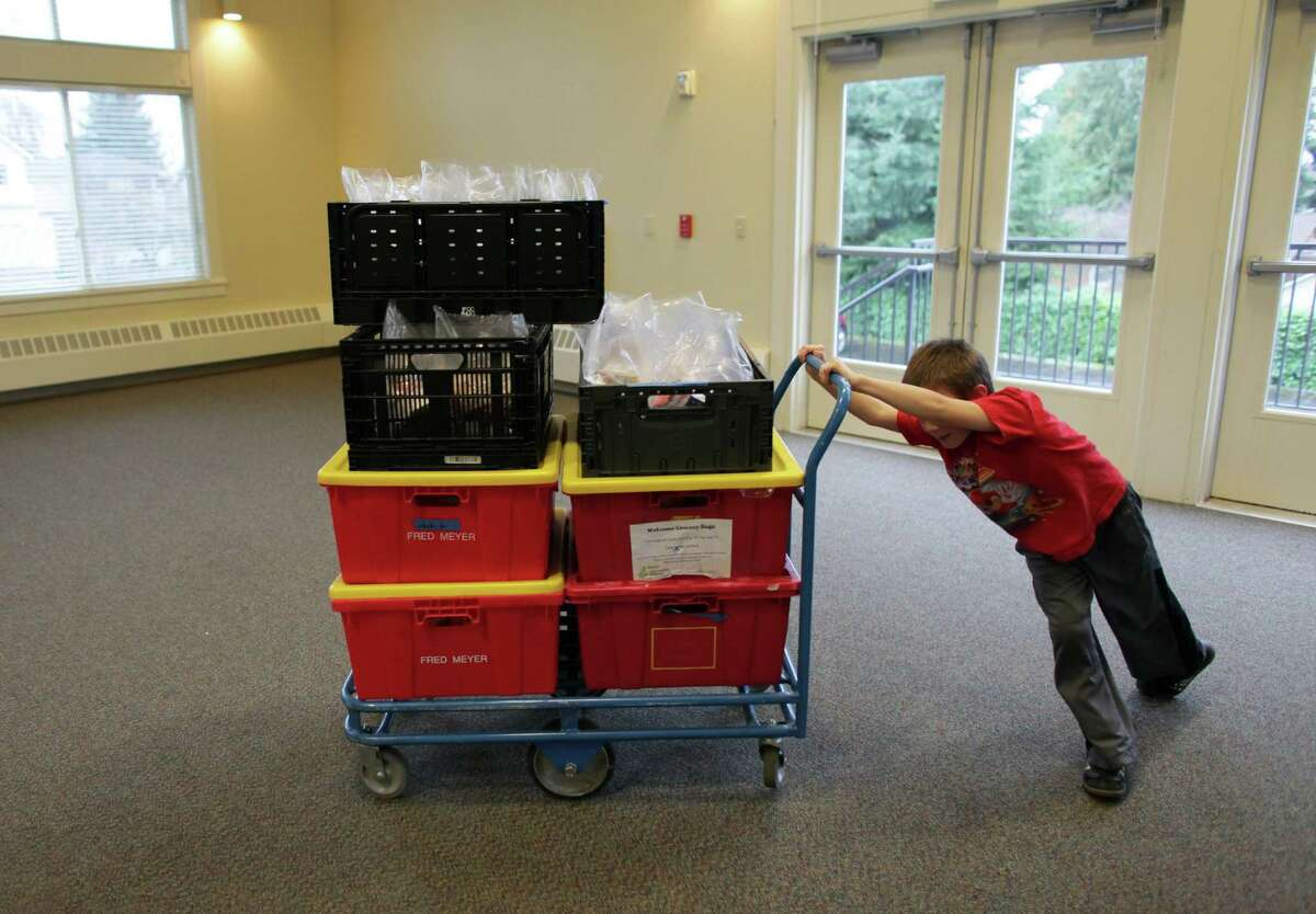 Julian Cummings, 8, pushes a cart of food during a