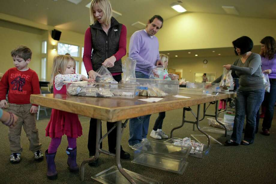 Dana Feaver works with her daughter Stella, 3, to pack food during a Healthy HIP Packs packing party. Photo: JOSHUA TRUJILLO / SEATTLEPI.COM