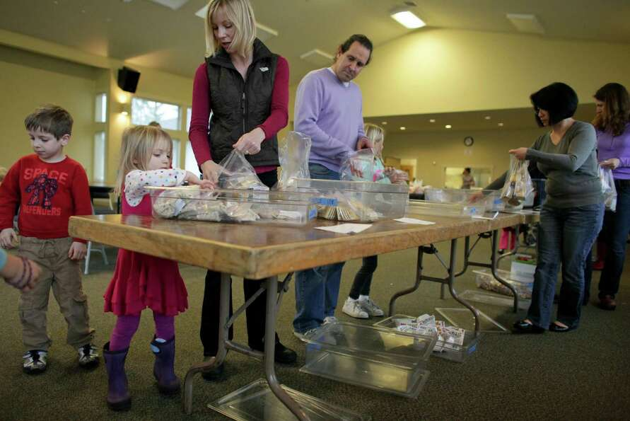 Dana Feaver works with her daughter Stella, 3, to pack food during a Healthy HIP Packs packing party