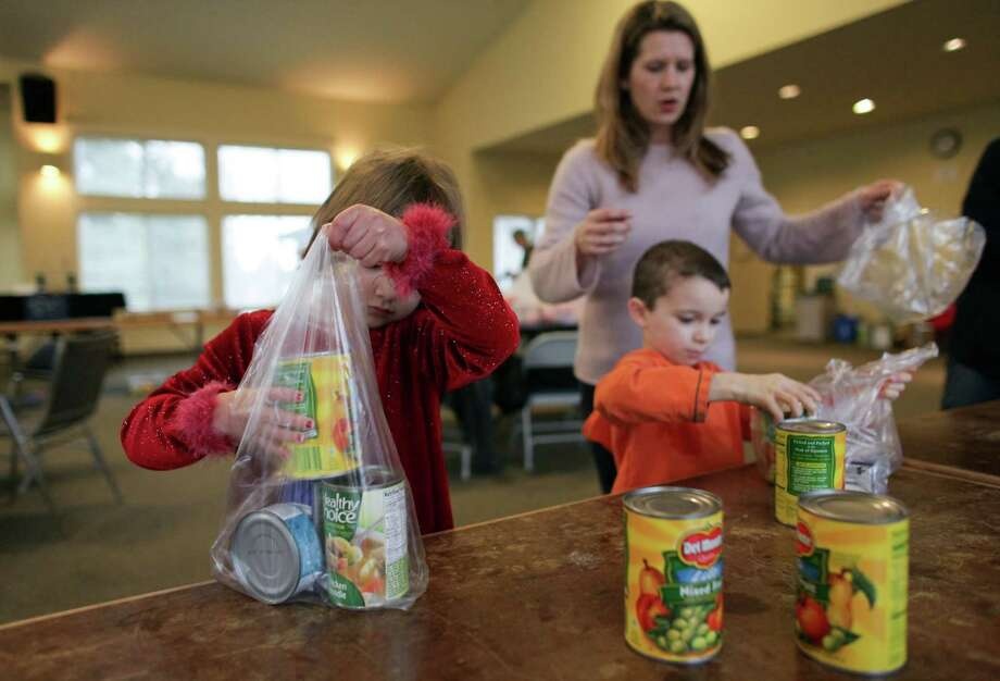 Volunteers, including Harmony and Evan Coppi, pack food. Photo: JOSHUA TRUJILLO / SEATTLEPI.COM