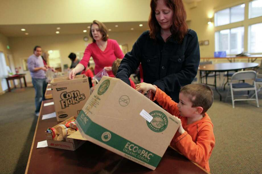 Evan Coppi, 6, and Kristi Coppi pack food for low-income students. Photo: JOSHUA TRUJILLO / SEATTLEPI.COM
