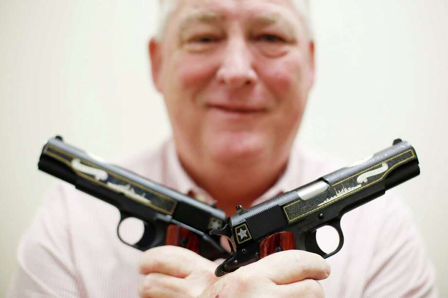 Bruce Bramlett, executive director of the Battleship Texas Foundation, displays a pair of the commemorative pistols being offered for sale to collectors in observance of the centennial of ship's commissioning ceremony. Photo: TODD SPOTH, Photographer / Todd Spoth