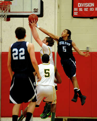 Trinity Catholic's #21 Dan O'Leary stops a layup by Wilton's #5 Olandi LeGrand, during FCIAC boys basketball semifinals action in Fairfield, Conn. on Tuesday February 26, 2013. Photo: Christian Abraham / Connecticut Post