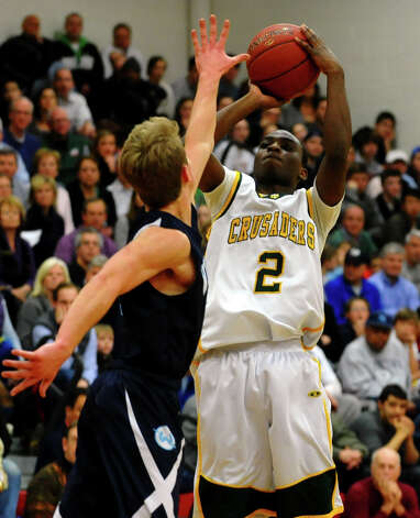 Trinity Catholic's #2 Schadrac Casimir attempts a shot of Wilton's #3 Max Maudsley, during FCIAC boys basketball semifinals action in Fairfield, Conn. on Tuesday February 26, 2013. Photo: Christian Abraham / Connecticut Post