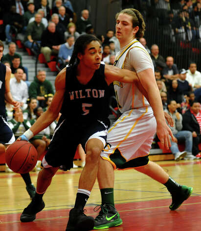 Wilton's #5 Olandi LeGrand tries to take the rebound he snagged past Trinity Catholic's #21 Dan. O'Leary, during FCIAC boys basketball semifinals action in Fairfield, Conn. on Tuesday February 26, 2013. Photo: Christian Abraham / Connecticut Post