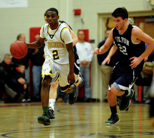 Trinity Catholic's #2 Schadrac Casimir drives the ball, during FCIAC boys basketball semifinals action against Wilton in Fairfield, Conn. on Tuesday February 26, 2013. Photo: Christian Abraham / Connecticut Post