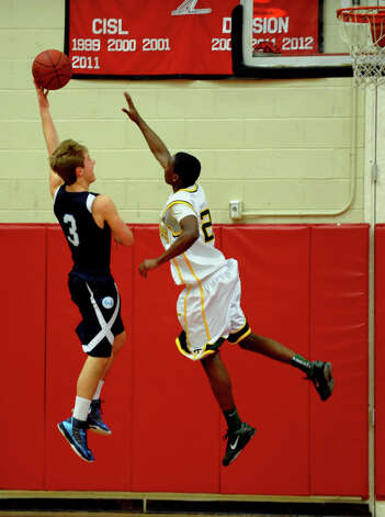 Trinity Catholic's #2 Schadrac Casimir looks to block a shot by Wilton's #3 Max Maudsley, during FCIAC boys basketball semifinals action in Fairfield, Conn. on Tuesday February 26, 2013. Photo: Christian Abraham / Connecticut Post