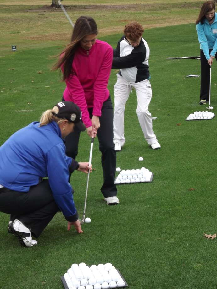 Erin Kenny of Citibank receives instruction from Lisa Fleming Edgmon, a teacher based at Shadow Hawk Golf Club in Richmond. Photo: Handout