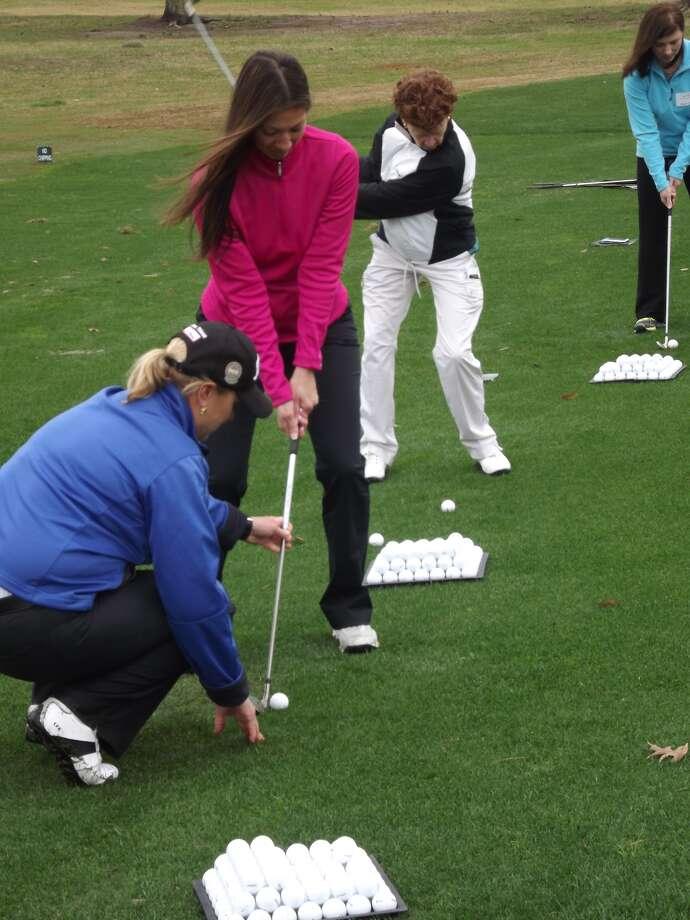 Erin Kenny of Citibank receives instruction from Lisa Fleming Edgmon, a teacher based at Shadow Hawk Golf Club in Richmond. Photo: Handout