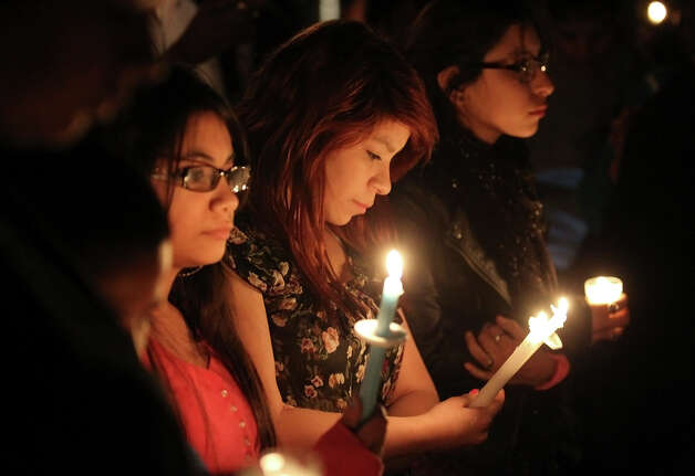 Mourners gather with candles during a vigil for a mother and her one-year-old twin boys who perished in a fire at 8153 Pearsall Road on Tuesday, Feb. 26, 2013. Roxanne Ordonez and her twin boys, Daniel and Orlin, perished from a fire fueled by high winds on Monday afternoon. Several hundred gathered at the burned out site to pay their respects for the victims. Photo: Kin Man Hui, San Antonio Express-News / © 2012 San Antonio Express-News