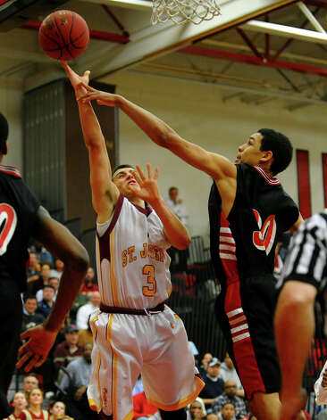 Central's #30 Maumer Cecunjanin disrupts a shot by St. Joseph's #3 Jake Pelletier, during FCIAC boys basketball semifinals action in Fairfield, Conn. on Tuesday February 26, 2013. Photo: Christian Abraham / Connecticut Post