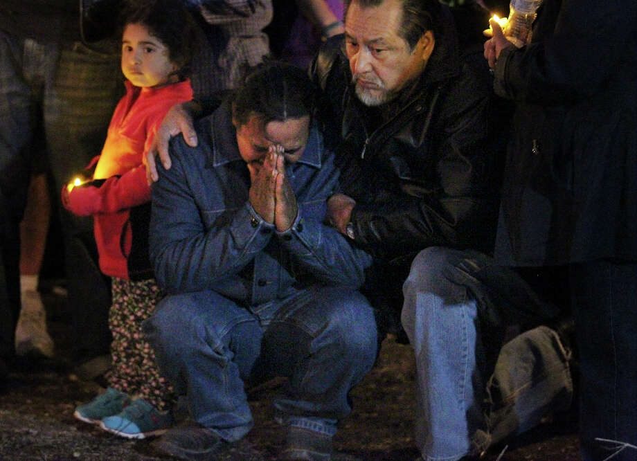 Orlin Ordonez, middle,  father of one year old twins Daniel and Orlin, grieves at the site during a vigil on Tuesday, Feb. 26, 2013. Several hundred people gathered at the property where Roxanne Cortez and her one-year-old twin sons, Daniel and Orlin, perished from a Monday afternoon blaze fueled by high winds. People huddled together with candles and said prayers to mourn the victims. Photo: Kin Man Hui / ©2013 San Antonio Express-News