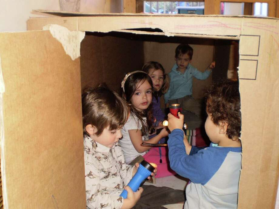 Students at Toddlertime Nursery School play with flashlights inside a cardboard box. The school will host Marc Armitage, who will discuss the importance of play, on March 19. Photo: Contributed Photo
