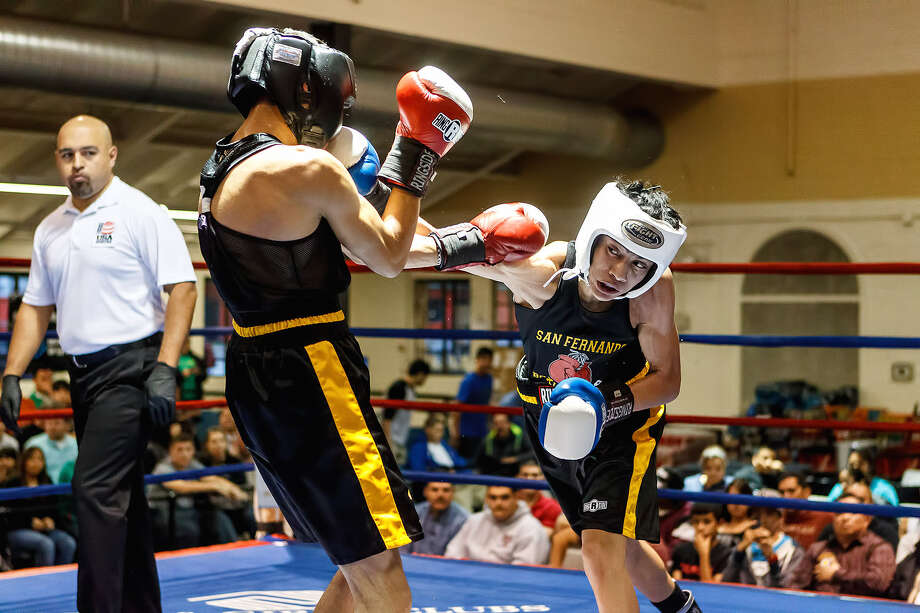Sixteen-year-old flyweight Hector Tanajara (right) of San Antonio Parks and Rec, landing a punch to Esiquiel Garcia last week at the Regional Golden Gloves, is one of 10 South Texans headed to state. Photo: Marvin Pfeiffer/ For The Express-News