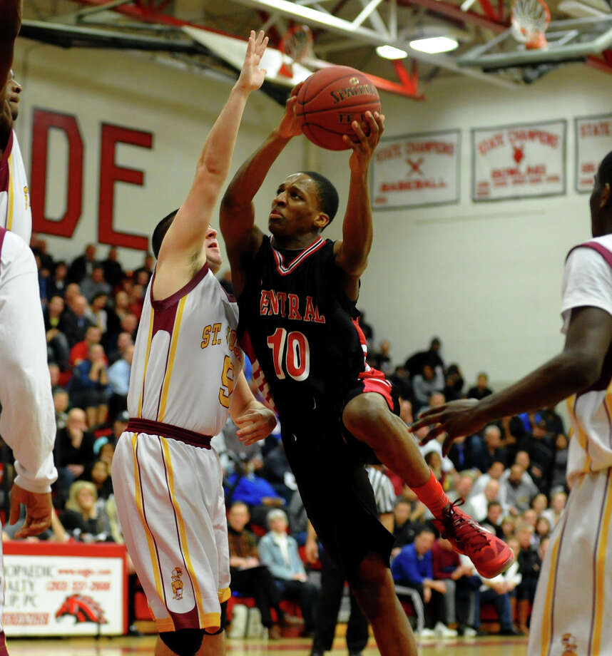 Central's #10 ShaQuan Bretoux goes to the net as St. Joseph's #5 Jonathan Dzurenda defends, during FCIAC boys basketball semifinals action in Fairfield, Conn. on Tuesday February 26, 2013. Photo: Christian Abraham / Connecticut Post