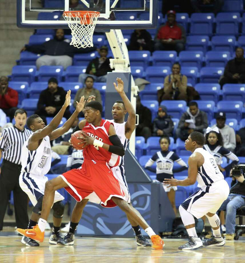 Mike Ross Connecticut Post freelance -Fairfield Prep's #44 Paschal Chukwu works his to the basket against three Hillhouse defenders during Tuesday evening SCC championship game.  Hillhouse would win 53-47. Photo: Mike Ross / www.mikerossphoto.com