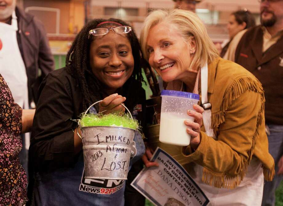Carolyn Campbell of News 92 FM poses with her loser's trophy after pulling the least amount of milk from her goat as Dana Tyson of Sunny 99.1 celebrates her win after pulling the most milk from her goat. Photo: Billy Smith II, Houston Chronicle / © 2013  Houston Chronicle