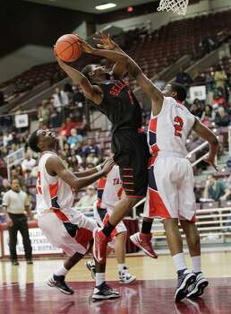 Bellaire's Crusz Ginnis Jr. is met by Alief Taylor's Martin Barron  as he attempts to drive to the basket during a Class 5A Region III quarterfinal basketball game Tuesday, February 26, 2013 at the M.O. Campbell Center in Houston. Photo: Bob Levey, Houston Chronicle / ©2013 Bob Levey