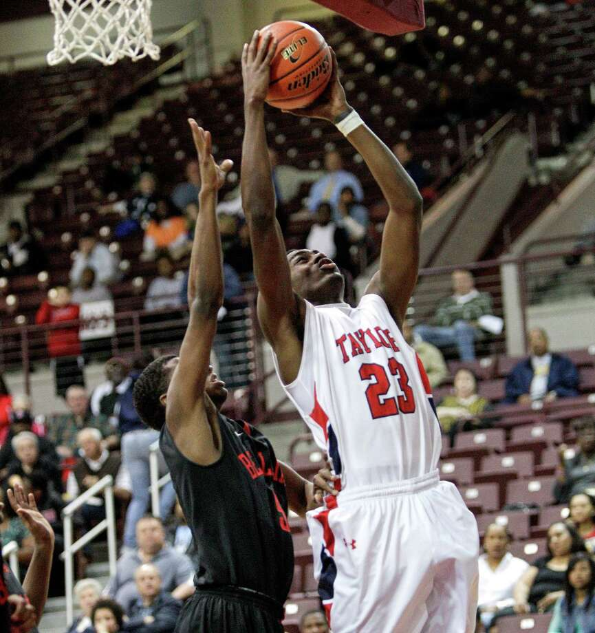 Alief Taylor's Keenen Brown #23 drives to the basket over Bellaire's Cruz Ginnis Jr. #5 during a Class 5A Region III quarterfinal basketball game Tuesday, February 26, 2013 at the M.O. Campbell Center in Houston. Photo: Bob Levey, Houston Chronicle / ©2013 Bob Levey
