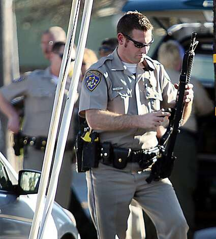 A California Highway Patrol officer loads an ammunition clip into his rifle near the shooting scene in Santa Cruz, Calif., where two Santa Cruz Police detectives were shot and killed Tuesday, Feb. 26, 2013. The shooting in the community about 60 miles south of San Francisco took place as police were investigating a report of a sexual assault,  Santa Cruz County Sheriff Phil Wowak said. A suspect was shot while police were in pursuit of the shooter, the sheriff said. Authorities said that person also died. (AP Photos/Santa Cruz Sentinel, Dan Coyro) Photo: Dan Coyro, Associated Press