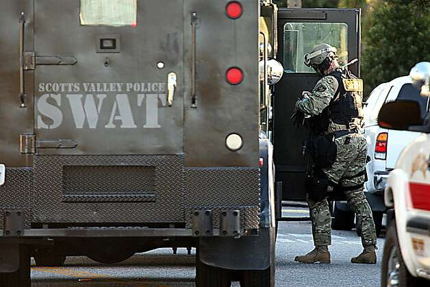 Santa Cruz County Sheriff's Deputy member of the SWAT team gears up to enter the shooting scene Tuesday, Feb. 26, 2013 where two Santa Cruz Police detectives were shot and killed. The shooting in the community about 60 miles south of San Francisco took place as police were investigating a report of a sexual assault,  Santa Cruz County Sheriff Phil Wowak said. A suspect was shot while police were in pursuit of the shooter, the sheriff said. Authorities said that person also died. (AP Photos/Santa Cruz Sentinel, Dan Coyro) Photo: Dan Coyro, Associated Press