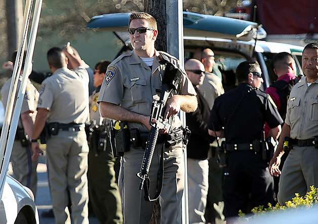 A California Highway Patrol officer carries his rifle near the shooting scene in Santa Cruz, Calif., where two Santa Cruz Police detectives were shot and killed Tuesday, Feb. 26, 2013. The shooting in the community about 60 miles south of San Francisco took place as police were investigating a report of a sexual assault,  Santa Cruz County Sheriff Phil Wowak said. A suspect was shot while police were in pursuit of the shooter, the sheriff said. Authorities said that person also died. (AP Photos/Santa Cruz Sentinel, Dan Coyro) Photo: Dan Coyro, Associated Press