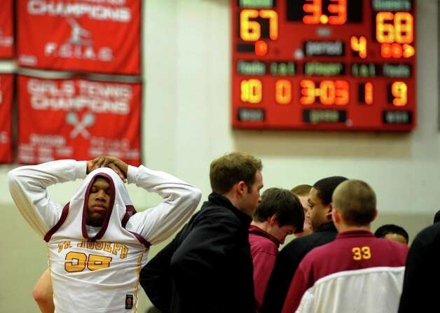 While the team has its final time out, St. Joseph's #35 Erick Langston reacts in the final seconds of play, during FCIAC boys basketball semifinals action against Central in Fairfield, Conn. on Tuesday February 26, 2013. Photo: Christian Abraham / Connecticut Post