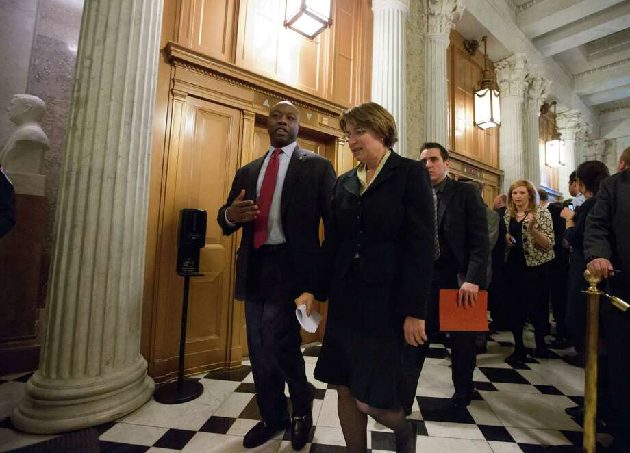 Sen. Tim Scott, R-S.C., and Sen. Amy Klobuchar, D-Minn., arrive for the final vote to confirm President Barack Obama's choice of Chuck Hagel to head the Defense Department after a protracted political fight, at the Capitol in Washington, Tuesday, Feb. 26, 2013.  (AP Photo/J. Scott Applewhite) Photo: J. Scott Applewhite