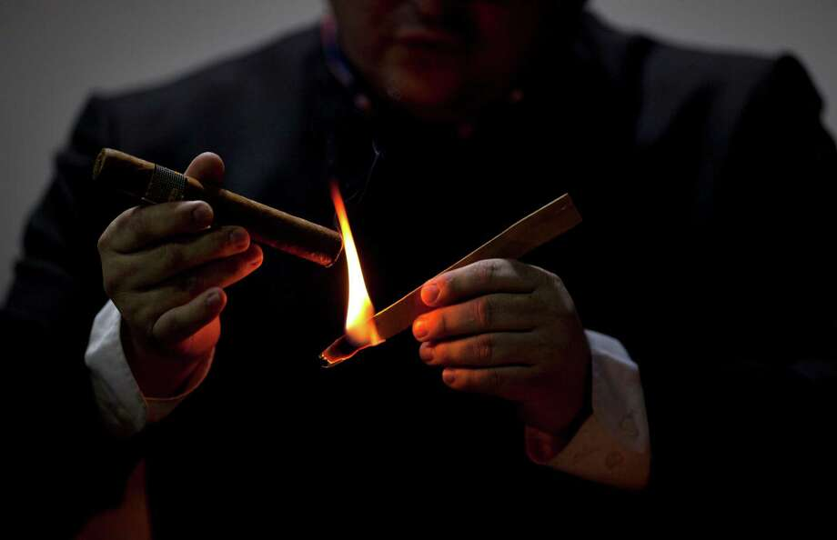 A man lights a cigar during the inauguration of the 15th Cigar Festival in Havana, Cuba, Tuesday, Feb. 26, 2013. Cigar enthusiasts from around the world come to Cuba during the annual celebration to visit tobacco farms and factories and savor new cigar brands. Photo: Ramon Espinosa, Associated Press / AP