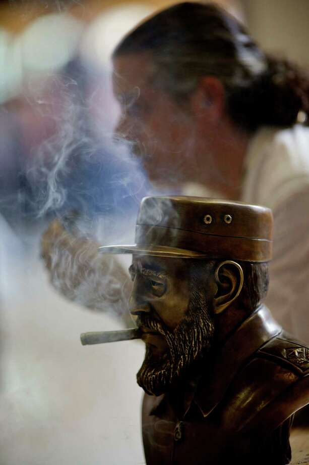 A bronze statue depicting Cuba's leader Fidel Castro smoking, made by the Cuban artist Ernesto Milanes, background, is seen during the inauguration of the 15th Cigar Festival in Havana, Cuba, Tuesday, Feb. 26, 2013. Photo: Ramon Espinosa, Associated Press / AP