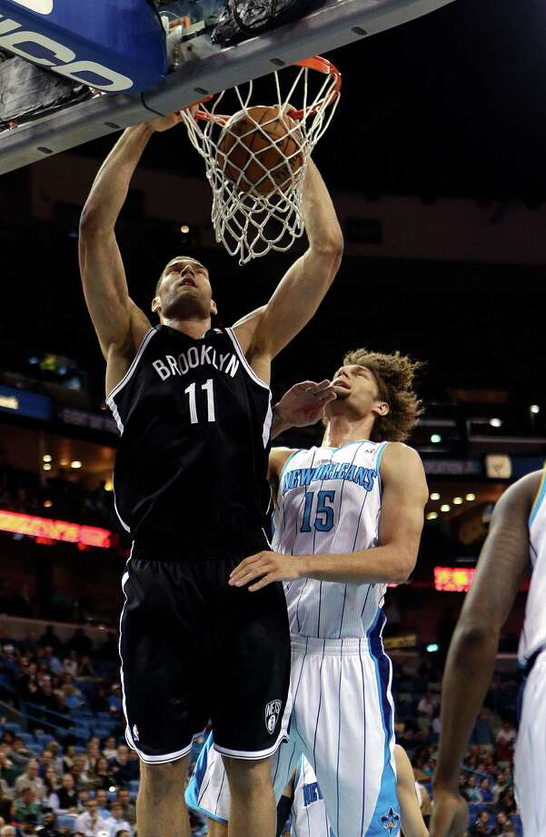 Brooklyn Nets center Brook Lopez (11) slam dunks over his twin brother, New Orleans Hornets center Robin Lopez (15) in the first half of an NBA basketball game in New Orleans, Tuesday, Feb. 26, 2013. (AP Photo/Gerald Herbert) Photo: Gerald Herbert