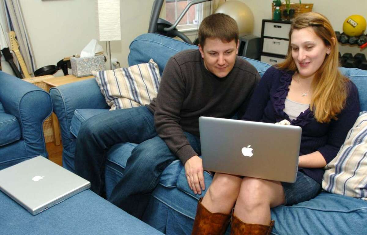 Matt and Bonnie Dewkett, of Danbury, looks over clients files at their home Monday, Dec. 28, 2009.