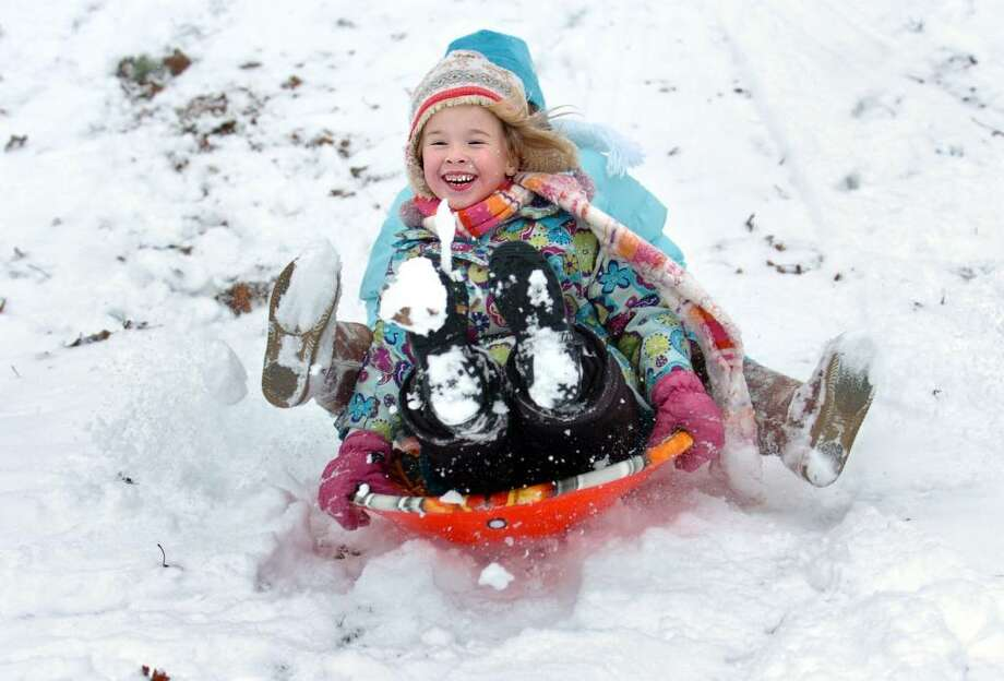 Six-year-old Payton Rahn sits in front of seven-year-old Arity Morrison, of Orange, as they sled down the hill Thursday at the Ansonia Nature Center during their Winter Holiday Nature Days program. Photo: Autumn Driscoll / Connecticut Post