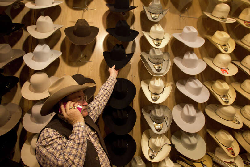 Rich Bishop places a hat on the rack at his booth Western Tradition during the Houston Livestock Sho