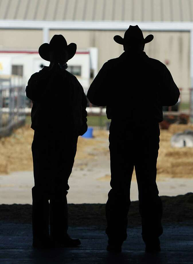 Two men look outside a loading ramp entrance to Reliant Center during the Houston Livestock Show and Rodeo in Reliant Park Tuesday, Feb. 26, 2013, in Houston. Photo: James Nielsen, Houston Chronicle / © 2013  Houston Chronicle