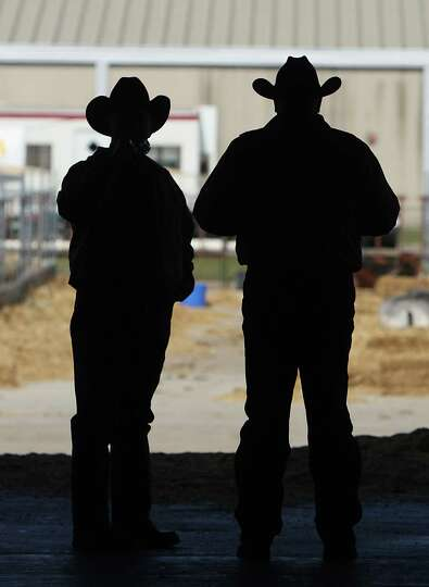 Two men look outside a loading ramp entrance to Reliant Center during the Houston Livestock Show and