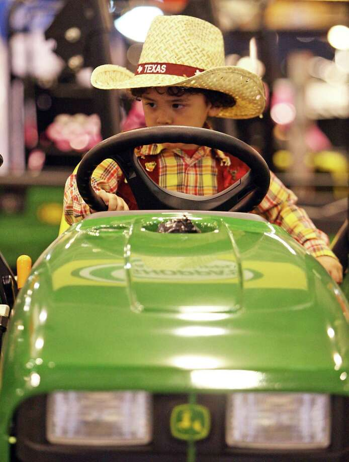 Three-year-old Justin Garcia sits on a John Deere 3032E tractor at the Shoppa's Farm Supply booth during the Houston Livestock Show and Rodeo in Reliant Park Tuesday, Feb. 26, 2013, in Houston. Photo: James Nielsen, Houston Chronicle / © 2013  Houston Chronicle