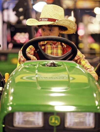 Three-year-old Justin Garcia sits on a John Deere 3032E tractor at the Shoppa's Farm Supply booth du