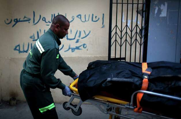 "An Egyptian paramedic evacuates the body of a slain foreign tourist to be transferred to Cairo, at the morgue of the Luxor International Hospital, in Luxor, Egypt, Tuesday, Feb. 26, 2013. A hot air balloon flying over Egypt's ancient city of Luxor caught fire and crashed into a sugar cane field on Tuesday, killing at least 19 foreign tourists in one of the world's deadliest ballooning accidents and handing a new blow to Egypt's ailing tourism industry. Arabic on the wall reads, ""we will all return to God, there no God but Allah, and Muhammed is his prophet."" (AP Photo/Nasser Nasser) Photo: Nasser Nasser"