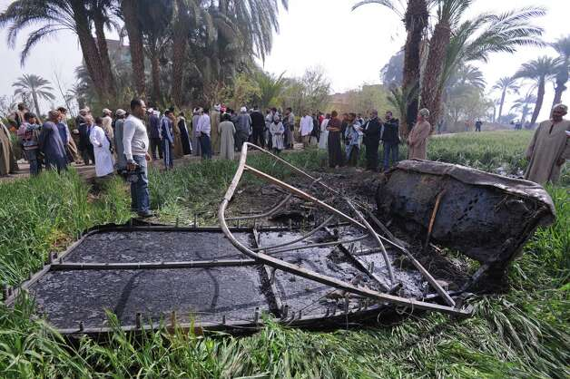 Egyptians gather at the site of a balloon crash where the remains of the burned gondola are seen, outside al-Dhabaa village, just west of the city of Luxor, 510 kilometers (320 miles) south of Cairo, Egypt, Tuesday, Feb. 26, 2013. A hot air balloon flying over Egypt's ancient city of Luxor caught fire and crashed into a sugar cane field on Tuesday, killing at least 18 foreign tourists, a security official said. The casualties included French, British, Belgian, Hungarian, Japanese nationals and nine tourists from Hong Kong, Luxor Governor, Saad told reporters. (AP Photo/Hagag Salama) Photo: Hagag Salama