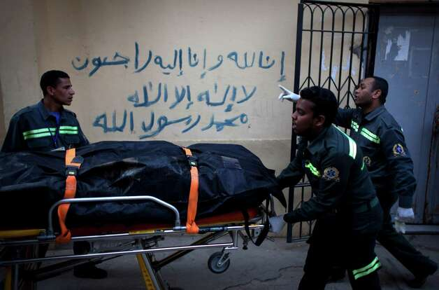 "Egyptian paramedics evacuate the body of a slain foreign tourist to be transferred to Cairo, at the morgue of the Luxor International Hospital, in Luxor, Egypt, Tuesday, Feb. 26, 2013. A hot air balloon flying over Egypt's ancient city of Luxor caught fire and crashed into a sugar cane field on Tuesday, killing at least 19 foreign tourists in one of the world's deadliest ballooning accidents and handing a new blow to Egypt's ailing tourism industry. Arabic on the wall reads, ""we will all return to God, there is no God but God, and Muhammed is his prophet."" (AP Photo/Nasser Nasser) Photo: Nasser Nasser"