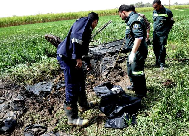 Egyptian rescue workers collect remains at the scene of a balloon crash outside al-Dhabaa village, just west of the city of Luxor, 510 kilometers (320 miles) south of Cairo, Egypt, Tuesday, Feb. 26, 2013. A hot air balloon flying over Egypt's ancient city of Luxor caught fire and crashed into a sugar cane field on Tuesday, killing at least 19 foreign tourists, a security official said. (AP Photo/Ibrahim Zayed) Photo: Ibrahim Zayed
